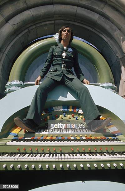 Drummer Keith Moon of The Who sitting on a theatre organ on the set of Ken Russell's film version of the group's 'rock opera' 'Tommy' 1975