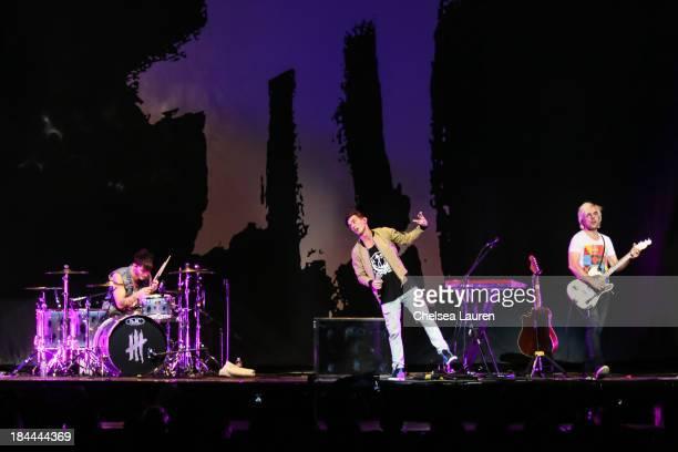 Drummer Louis Vecchio vocalist David Boyd and guitarist Soren Hansen of New Politics perform at Staples Center on October 13 2013 in Los Angeles...