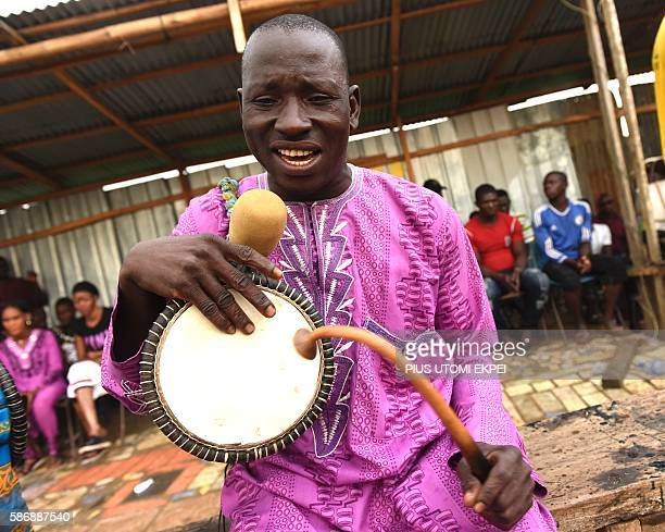 A drummer performs during a dambe match at KaraIsheri in Ogun State southwest Nigeria on July 24 2016 Dambe is a traditional boxing associated with...