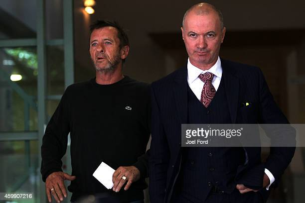 Drummer Phil Rudd leaves Tauranga District Court with lawyer Craig Tuck after being arrested in relation to breach of bail conditions on December 4,...