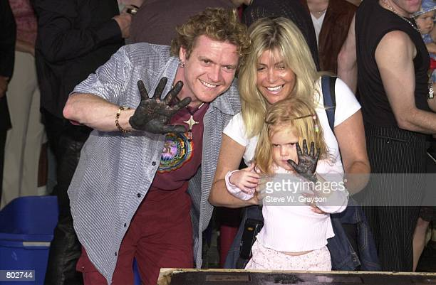 Drummer Rick Allen of Def Leppard with his wife and daughter pose for photgraphers after their induction to the Rock Walk of Fame at the Guitar...