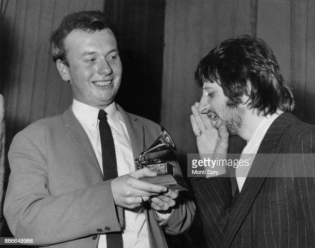 Drummer Ringo Starr of English rock band the Beatles congratulates EMI recording studio audio engineer Geoff Emerick on his Grammy Award at the EMI...