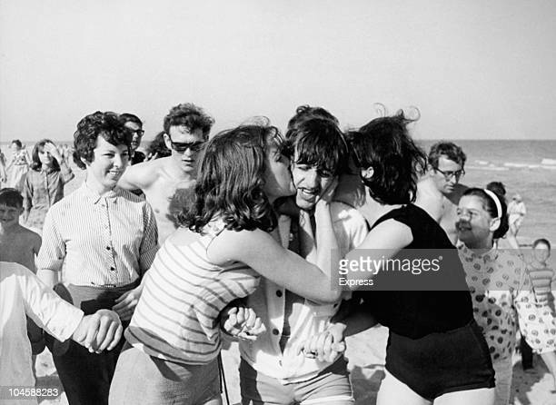 Drummer Ringo Starr of The Beatles on a beach in Miami Florida getting kissed by female fans circa February 1964
