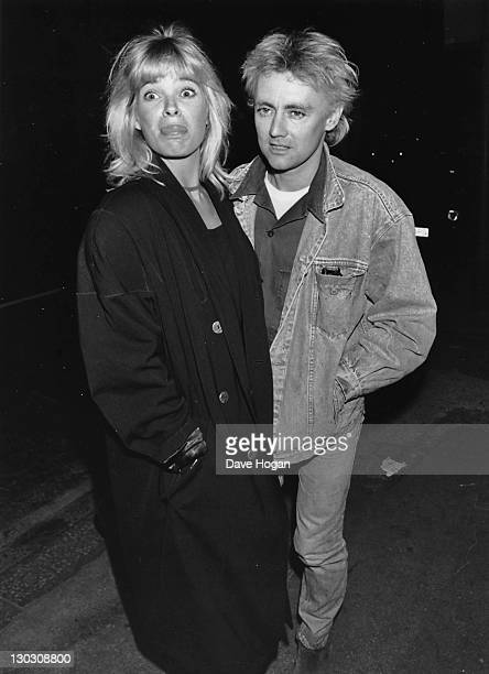 Drummer Roger Taylor of British rock band Queen leaves Brown's nightclub in London with his girlfriend Debbie Leng April 1988