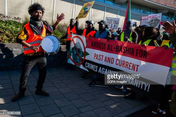 A drummer seen before protesters holding a banner and placards during the demonstration The coordination committee 'Sudan Unite' in the Netherlands...