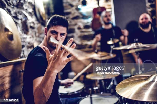 drummer showing stick spinning tricks while recording with band - heavy metal stock-fotos und bilder