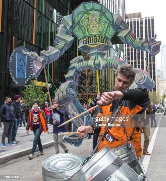 A drummer takes part in a protest in front of a Amazoncom CEO Jeff Bezos effigy outside of the Amazoncom headquarters on May 1 2017 in Seattle...