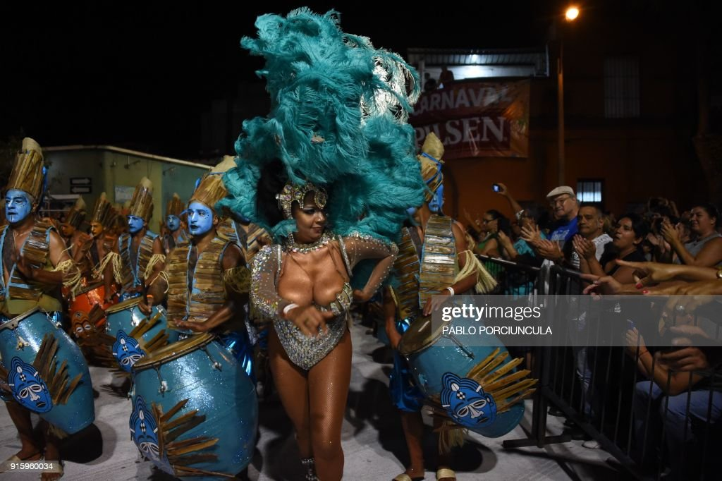 Drummers and dancers forming part of a group known as a 'comparsa' compete by playing and dancing to the rhythm of the traditional 'candombe' music, in Montevideo on February 8, 2018, during the 'Llamadas', one of the events that make up Uruguay's carnival -- the world's longest. / AFP PHOTO / Pablo PORCIUNCULA