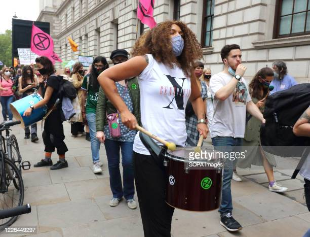 Drummers wearing facemasks create an atmosphere for the Extinction Rebellion march through Central London. Extinction Rebellion demonstrators march...