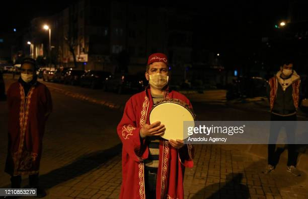 Drummers wearing traditional cloths besides protective face masks against the coronavirus pandemic awaken people for sahur meal the last meal before...