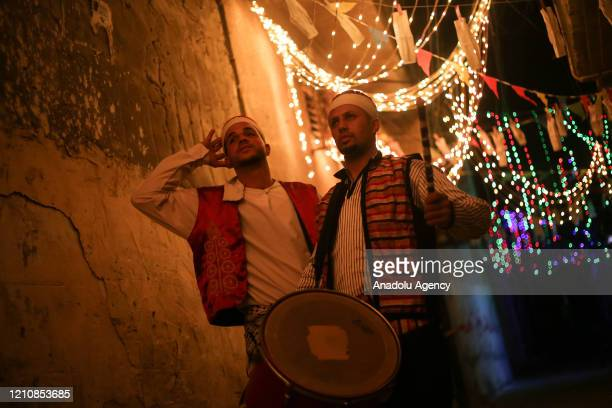 Drummers wearing traditional cloths play drums and read folk poetries to wake people for sahur meal the last meal before a long day of fasting that...