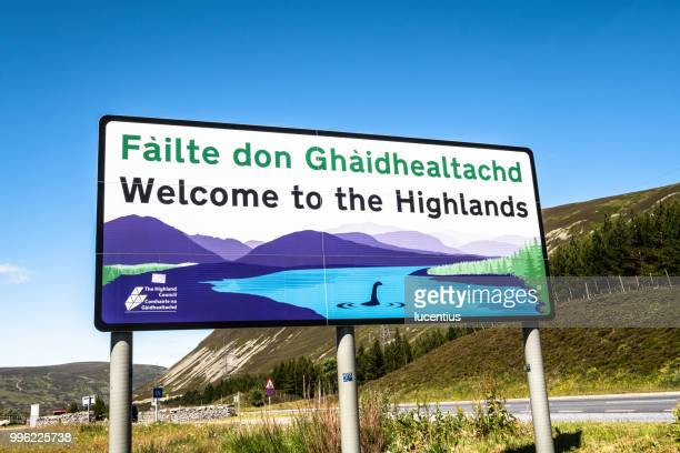 drumocter pass gaelic road sign, scotland - loch ness monster stock pictures, royalty-free photos & images