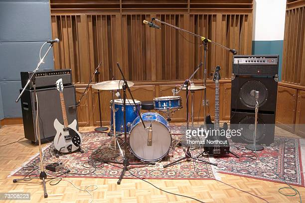 Drums and electric guitars plugged into amplifier in recording studio