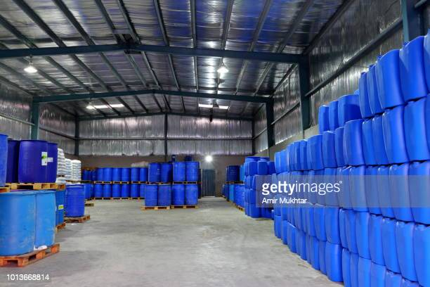 drums placed in a chemical factory godown racks - drum container stock photos and pictures