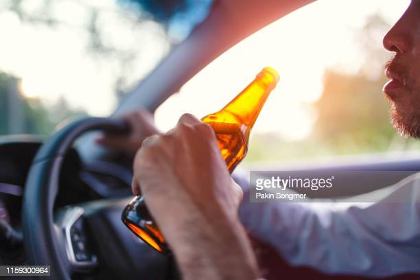 drunk asian young man drives a car with a bottle of beer - drinking and driving stock pictures, royalty-free photos & images