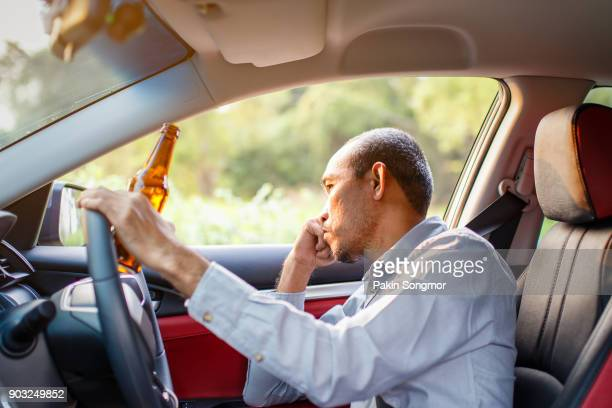 drunk asian young man drives a car with a bottle of beer - drinking and driving stock photos and pictures