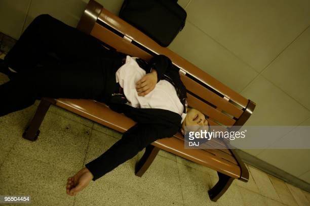 drunk businessman sleeping on bench at platform - 酔う ストックフォトと画像