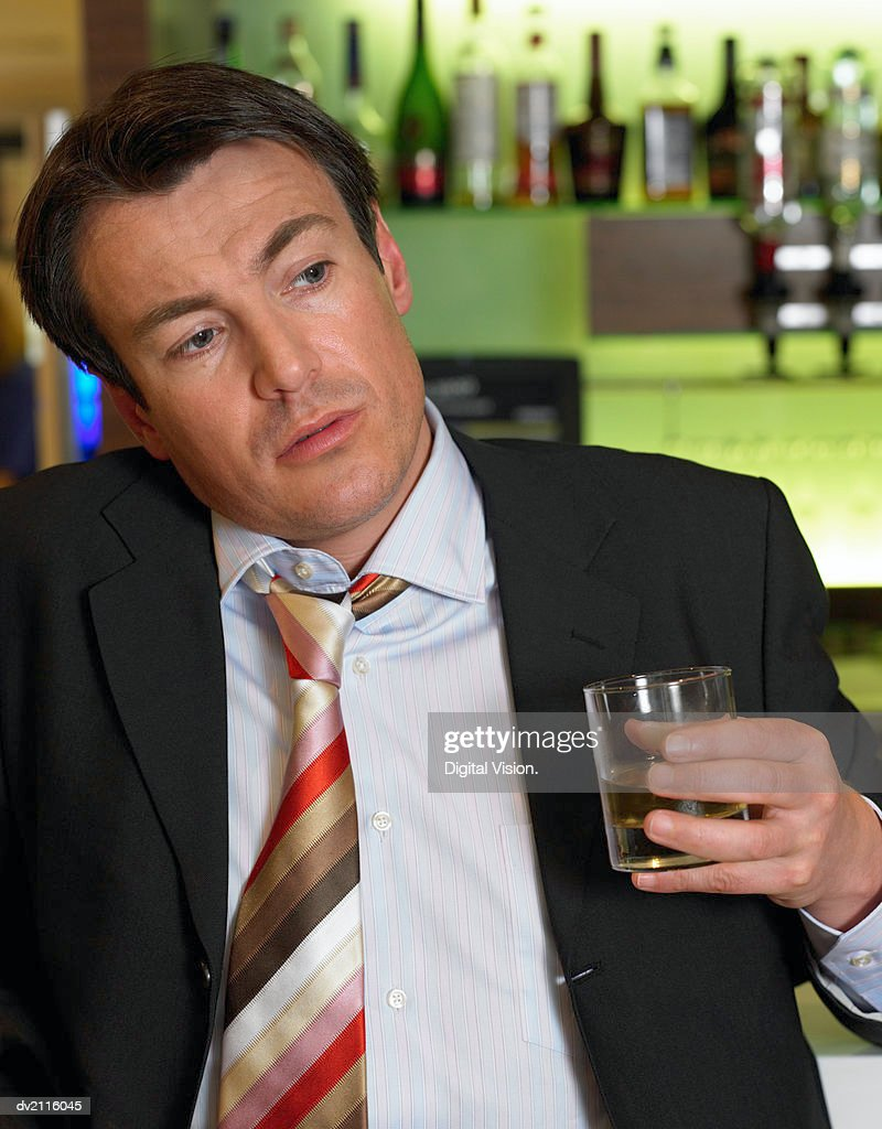 Drunk Businessman Standing by a Bar With a Whisky in His Hand : Stock Photo