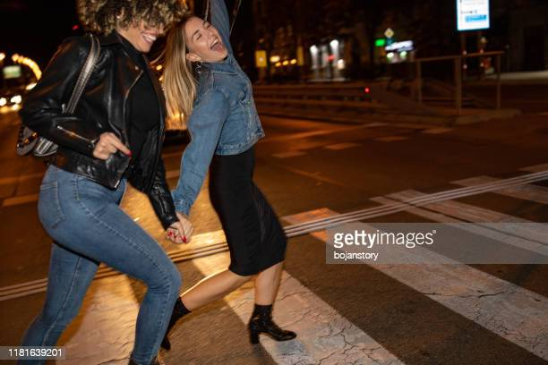 drunk female friends crossing the street - drunk woman stock pictures, royalty-free photos & images