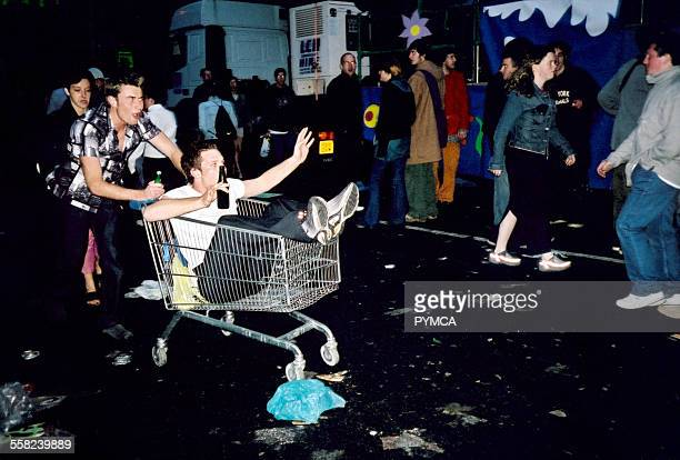 Drunk hijinks in shopping trolley in the street at night after Leeds Carnival Leeds UK 2000