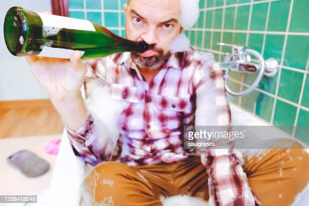 drunk man drinking in the bathtub - cleaning after party stock pictures, royalty-free photos & images