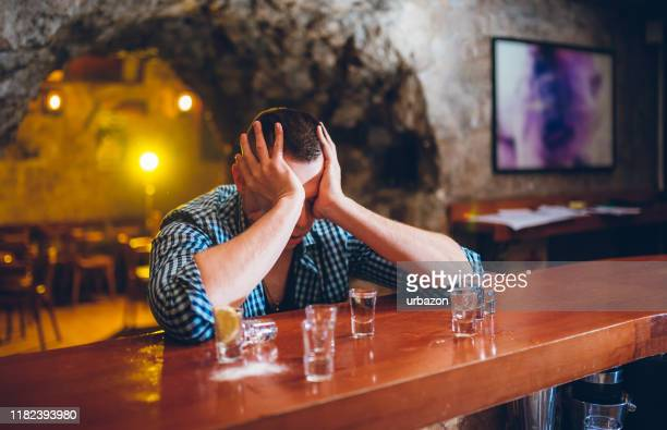 drunk man in bar - drunk stock pictures, royalty-free photos & images