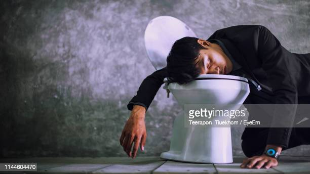 drunk man sleeping on toilet seat against wall - passed out drunk stock pictures, royalty-free photos & images