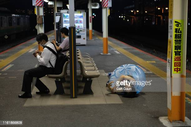 A drunk man wears an inflatable ring as he lies asleep on a train station platform on August 16 2019 in Ofuna Japan