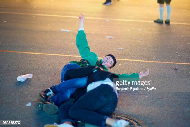 drunk men lying on road at amusement park during night - binge drinking stock photos and pictures