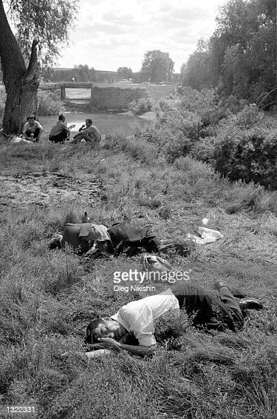 Drunk men sleep in the grass along the banks of a river during the Sabantuy holiday festival June 9 2001 in the village of Baltaci in the Tatarstan...