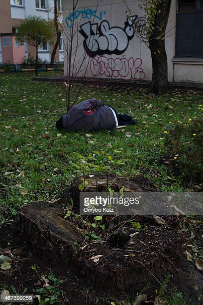 Drunk or intoxicated in some other way man sleeping on a street lawn between the tree and the tree stub, the graffiti on the wall in the background.
