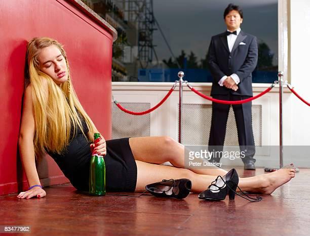 Drunk teenager asleep on night club floor