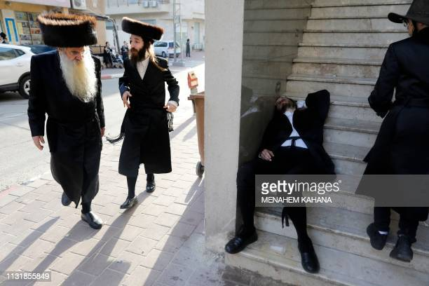 A drunk UltraOrthodox Jewish man lays on the street in the central Israeli city of Bnei Brak on March 21 2019 during the feast of Purim The...