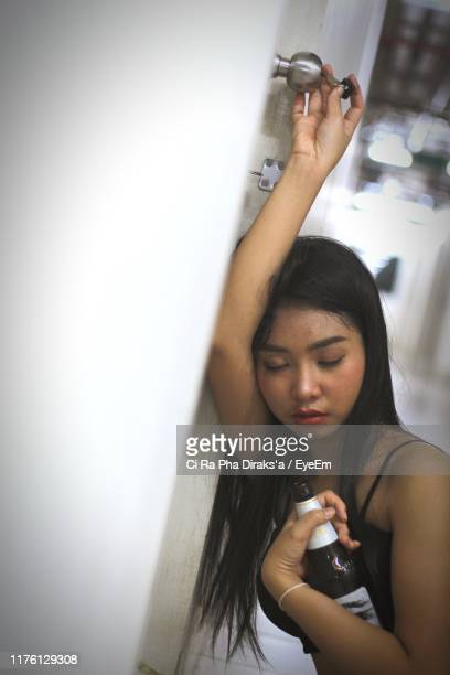 drunk woman holding bottle at home - drunk woman stock pictures, royalty-free photos & images