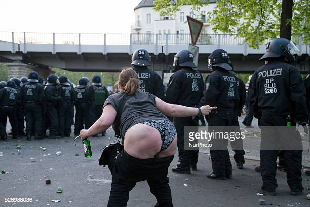 A drunk woman shows her derriere to the police during the clashes occurred between demonstrators and police in the Kreuzberg district on May 1 2016...