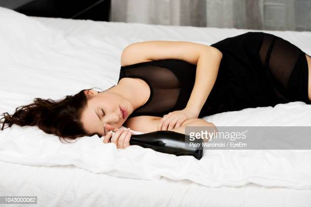 drunk woman with wine bottle sleeping on bed at home - drunk woman stock pictures, royalty-free photos & images