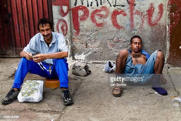 Drunken Colombian garbage recollector sleeps on the street in the slum of Calvario on 23 April 2004 in Cali, Colombia. Calvario, a slum right in the...