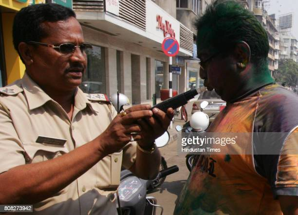 Drunken Driving Drink Driving Holi Festival Police officer check a reveller under Drunken Drive Test at Girgaon Chowpatty in Mumbai on Wednesday