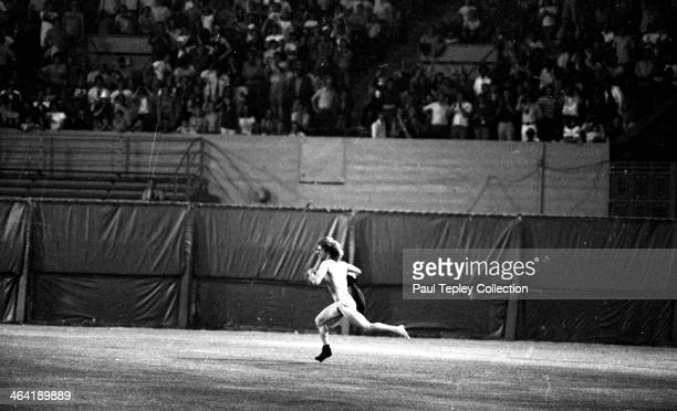 A drunken fan runs on the field during a game between the Texas Rangers and Cleveland Indians on June 4 1974 at Cleveland Municipal Stadium in...