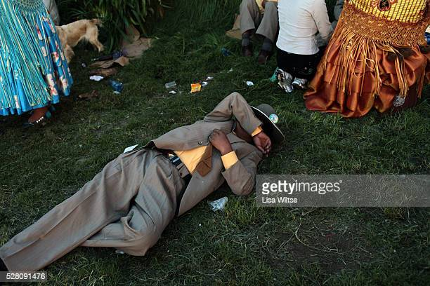 Drunken man passes out on the grass during One of Bolivia's most famous festivals, the festival of the Virgen de la Candelari, takes place in the...