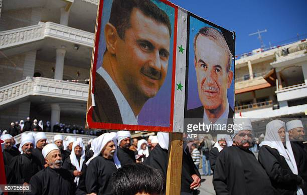 Druze boy holds portraits of Syrian president Bashar al-Assad , and his father, the former president Hafez al-Assad, during a rally marking the...