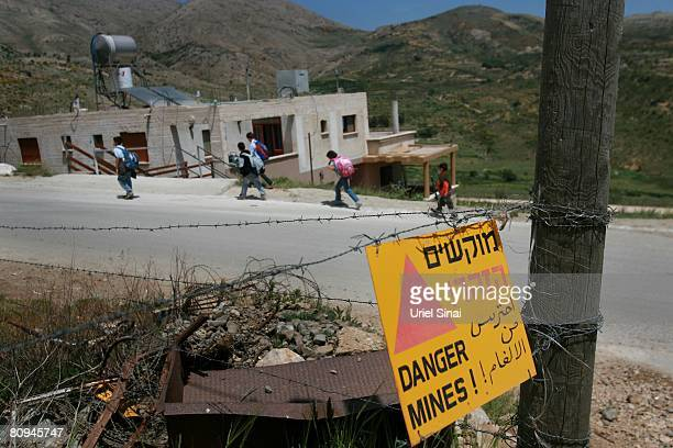 Druze children pass Israeli army signs warning of a minefield on their way home from school on April 29 2008 in Majdal Shams in the Golan Heights...