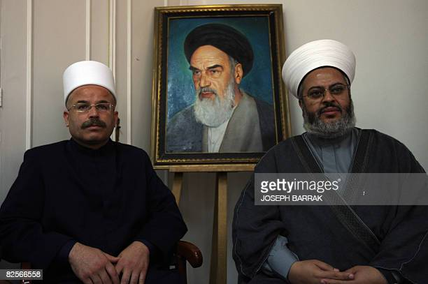 Druze cleric Sheikh Nazih alAridi and Sunni Muslim cleric Sheikh Zuheir Juaid sit in front of a framed portrait of Iran's late supreme leader...