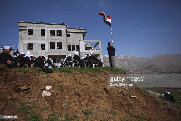 Druze man waves a Syrian flag as his community rallies close to the Syrian border in support the Damascus regime on February 14 2010 in Majdal Shams...