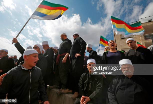 Druze men residing in Israel hold their community's flag after they heard about clashes in the Syrian Druze village of Hadar, on November 3, 2017 in...