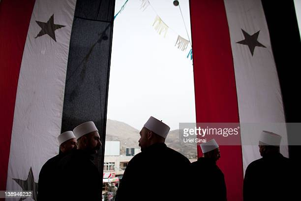 Druze men stand behind large Syrian flags as they take part in a rally, in the village of Majdel Shams near the border between Israel and Syria on...