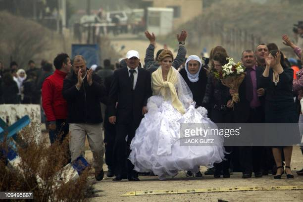 Druze Nabeeh Farhat from Buqata in the Israeli annexed Golan Heights escorts his Syrian bride Samar Khayal through the UN monitored no man's land at...