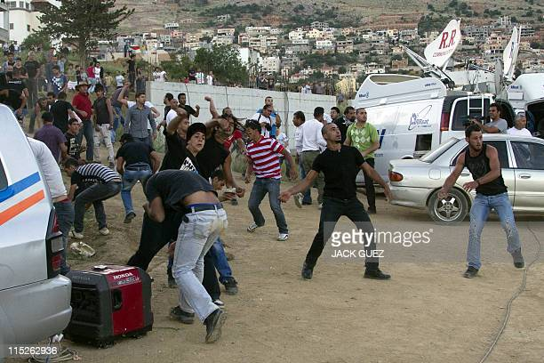 Druze residents from Majdal Shams hurl stones at the Israeli army blocking demonstrators as they gather along Syria's border with Israel while trying...