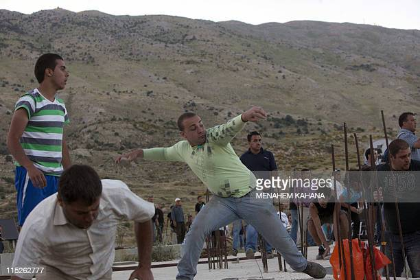 Druze residents of Majdal Shams hurl stones at the Israeli army blocking demonstrators as they gather along Syria's border with Israel while trying...