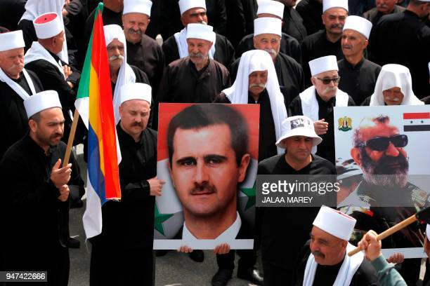 Druze residents of the Ein Qiniye village in the Israeli-occupied Golan Heights hold Syrian president's and Major General of the Syrian Republican...